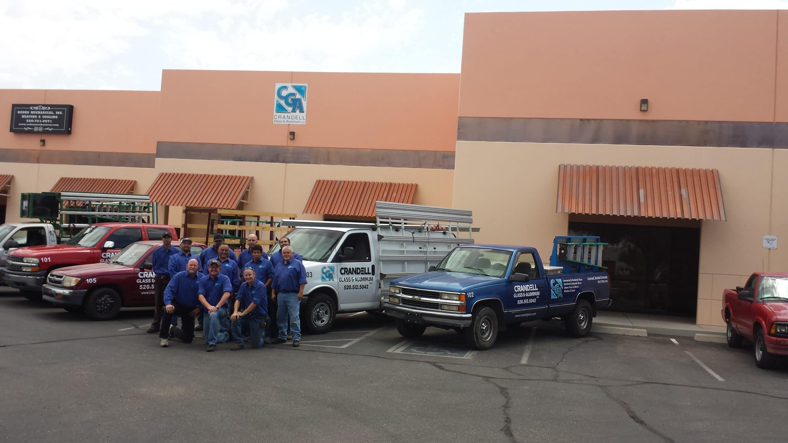 Crandell Glass employees and service trucks outside building