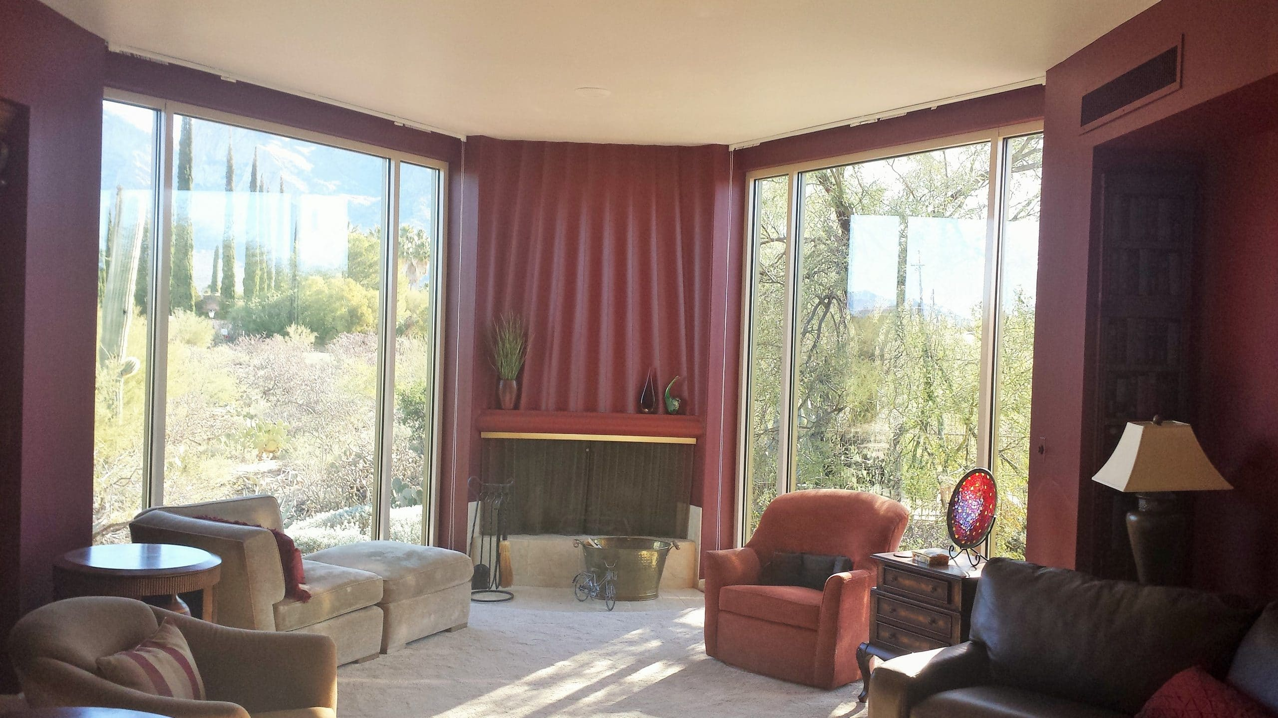 Fireplace in corner with floor to ceiling residential windows on either side