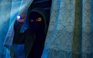 Burglar entering home through open window